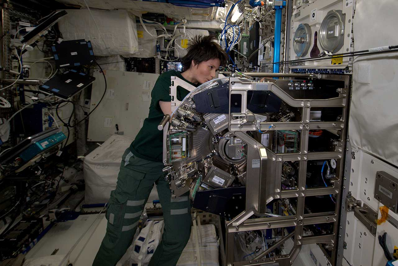 A photo of ESA astronaut Samantha Cristoforetti working in the International Space Station's Biolab facility.